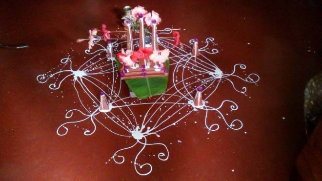 Mathevar is placed on a wooden platform decorated with flowers and rice flour designs: My Mother's handiwork!